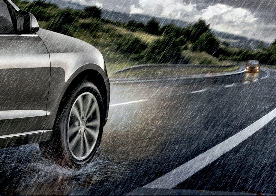 Voiture roulant sur une route mouillée et une pluie battante