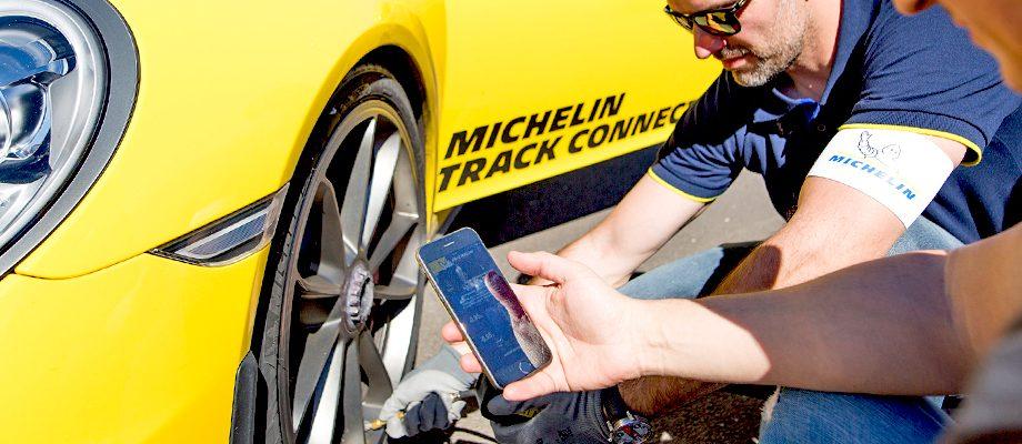 Deux personnes vérifient les pneus d'une voiture Michelin Track Connect
